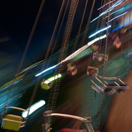 An amusement ride at Navy Pier in Chicago, in motion at night.