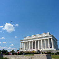 An exterior view of the Lincoln Memorial with a plane flying overhead.