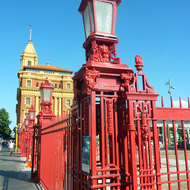A view of the Auckland ferry building and the red wrought iron fence built between 1913 and 1923, during one of the roughest periods of labor strife in New Zealand's history.