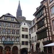 Half-timbered architecture of Strasbourg with the Cathedrale Notre-Dame de Strasbourg spire in the background.
