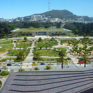 A view from the de Young Museum tower of the roof of the de Young Museum (foreground), the California Academy of Sciences (middle), the University of California, San Francisco (background) and the Sutro Tower (far background).