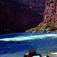 A private trip raft chafing against shore on the Colorado River in the Grand Canyon.