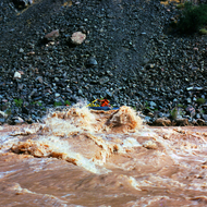 A whitewater raft at the top of a wave in Hermit Rapid.
