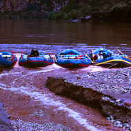 A small flash flood in a small Grand Canyon side stream empties into boats tied up to shore.