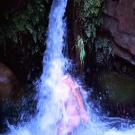 A rafter taking a shower in a Deer Creek waterfall.