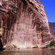 A river raft dwarfed by a cliff at the Yampa River confluence with the Green River.