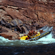 A 37-foot motor boat catching air in a House Rock rapid in the Grand Canyon.