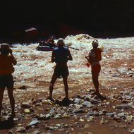 Two guides and a passenger watching a commercial raft avoid the hole in House Rock Rapid.