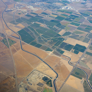 An aerial view of Central Valley farmland in California near Modesto, with Interstate Highways 5 (lower righthand corner) and 580 (going up the left side) as well as canals.