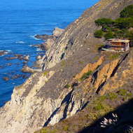 A cliff-hugging mansion on the rugged California coastline south of Monterey.