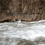 A private rafter running Granite Falls in the Grand Canyon.