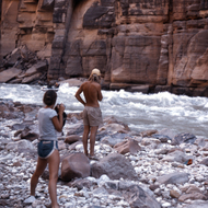 Private river guides watching one of their boats running Upset Rapid in the Grand Canyon.