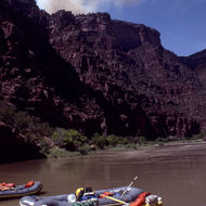 A private river trip on the Gates of Lodore section of the Green River, with a fire in the distance.