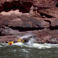 A Western River Expeditions pontoon boat running a rapid in the Grand Canyon.