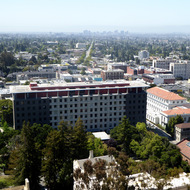 A view of UC Berkeley from the Campanile (bell tower) with Barrows Hall in the foreground and Telegraph Avenue leading to downtown Oakland in the background.