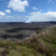 The Halema'uma'u Crater at the Hawai'i Volcanoes National Park on the Big Island across a lava field.