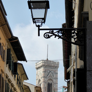 A Florence street scene with a tower of the Cathedral of Santa Maria del Fiore in the background.