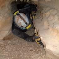 A caver squeezing through a tight passage.