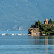 Early morning view of Lake Ohrid with Church of St. John and boats moored nearby.