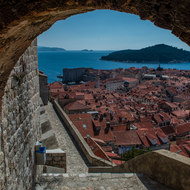 View of Dubrovnik and the sea through an arch in the city walls.