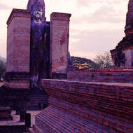 The sun sets behind a Buddha image in Sukhothai.