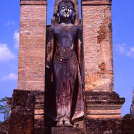 A Buddha stands in the ruins of a pagoda.