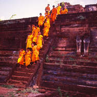 Young novice monks descend from the platform of a pagoda ruin.
