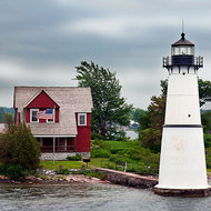 Windswept house with lighthouse on the St. Lawrence river.