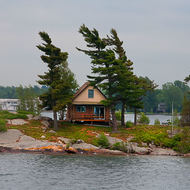 Home amongst the wind bent trees on the St. Lawrence river.