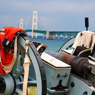 Old canon at Fort Michilimackinac and the Mackinac bridge.