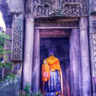 Standing Buddha image in the doorway of old pagoda.