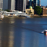 Eagle Street pier with City Cat, Customs House and red City Hopper commuter transport on the Brisbane River.