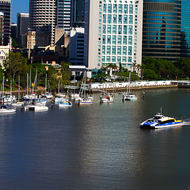 City Cat commuter transport powering up Brisbane River in front of downtown Brisbane.