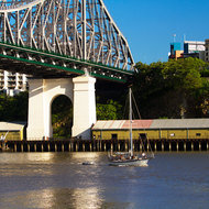 Yacht motoring down the Brisbane River under the Story Bridge.