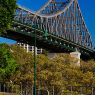Park bench under the Story Bridge on the bank of the Brisbane River.