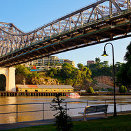 A City Hopper commuter transport passes under the Story Bridge on the Brisbane River.