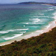 Surfers seeking the best breaks along Tallow Beach, south out Cape Byron.
