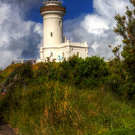 Cape Byron lighthouse in the early morning light with clouds and blue sky.