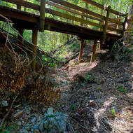 Dry creek bed under a wooden bridge.