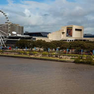Queensland Performing Arts Centre and the wheel of Brisbane in the South Bank parklands.