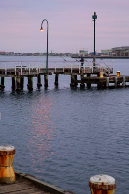 Thumbnail image ofDawn over Port Melbourne pier and a hopeful fisherman.