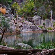 Stunning Coomba waterhole with colored granites and grasses.