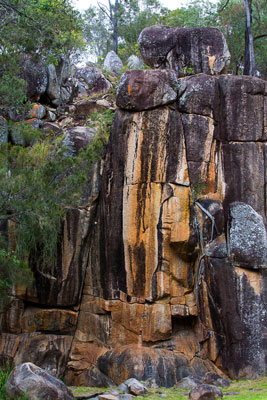 Thumbnail image of Colored granite hosting the roots of trees beside...
