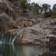 Coomba Falls over the granites into the waterhole on a grey winter's day.