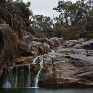 Falling rain dots the waterhole surface at Coomba Falls.
