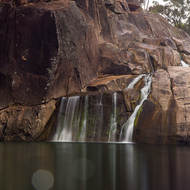 Coomba Falls and waterhole milky in a long exposure on a dull day.