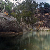 Milky falls and waterhole surrounded by stunning granite formations.