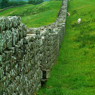 Double line of Hadrian's Wall stretches over the green pastures.