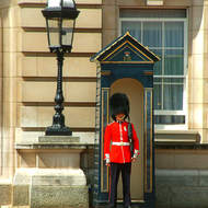 Busby hatted Buckingham Palace guard at the ready.