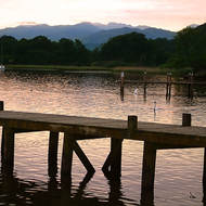 Sun setting over the hills beside Lake Windermere and the Ambleside jetty.